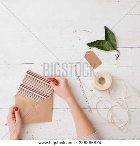 Top View On Woman's Hands Putting A Card Into A Craft Paper Envelope. Tag, Leaves, Pencil And Cord O