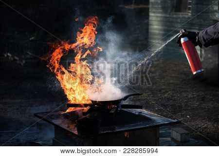 Man Extinguishing The Fire On An Iron Pan With Foam From A Spray Can, Demonstration During A Fire De