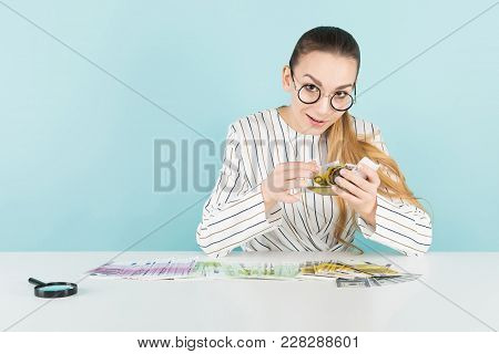 Portrait Of Attractive Woman In Striped Shirt And Eyeglasses Isolated On Blue Background With Magnif