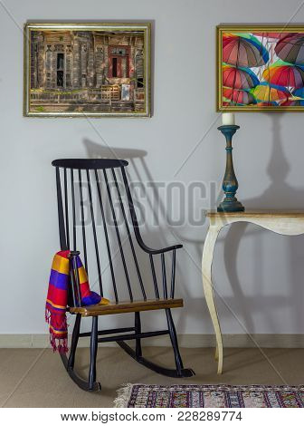 Interior Shot Of Vintage Rocking Chair, Old Style Table, Candlestick On Background Of Off White Wall