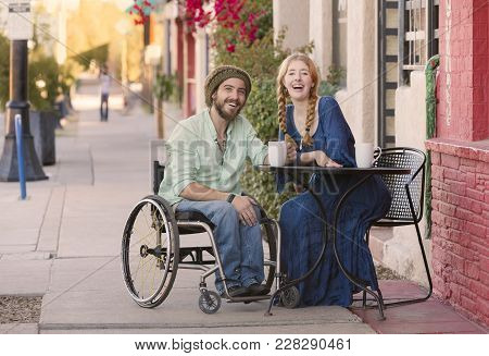 Woman Having Coffee With Friend In Wheelchair On Sidewalk
