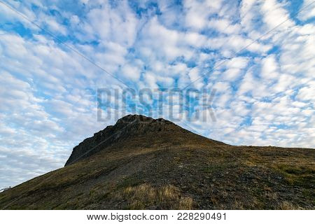 Beautiful Clouds Above Platafjellet In Summer. Svalbard. Rocky Hills With Blue Sky And White Clouds