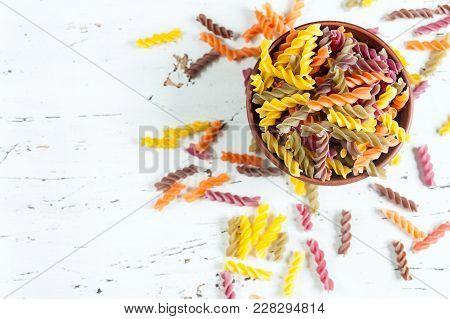 Colored Italian Fusilli Pasta In Bowl On White Wooden Table. Top View.