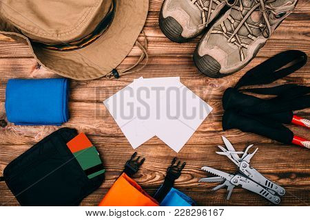 Top View Of Equipment For Hiking And Travel On Wooden Table With Empty Space In The Middle. Items In
