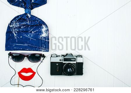 Funny Female Face Shape Made Of Headphones, Sunglasses And Camera On A White Wooden Table, Top View.
