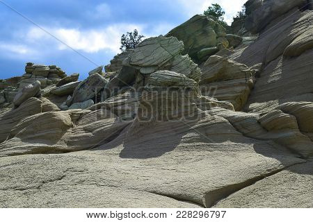 Green And Tan Colored Sandstone Boulders Exposed On Hillside.