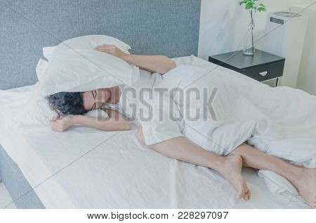 Young Caucasian Woman With Black Hair Sleeps Pressing Pillows To Her Ears And Head.  I Do Not Want T