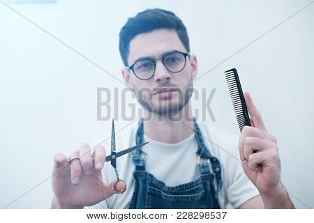 Men's Hairstyling And Haircutting With Hair Clipper In A Barber Shop Or Hair Salon. Focus On The Han