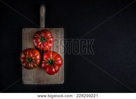 Raw Tomatoes On Cutting Board Over Black Stone  Background With Copy Space. Fresh Ripe Organic Tomat