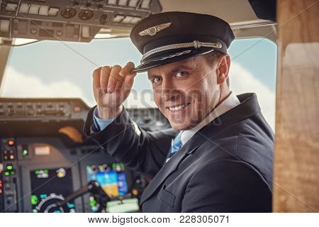 Portrait Of Beaming Pilot Holding Hat By Arm While They Looking At Camera. Occupation Concept