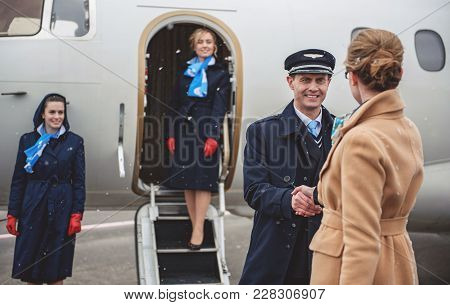 Cheerful Aviator Shaking Hands Young Businesswoman Near Plane. Happy Stewardesses Watching At Them.