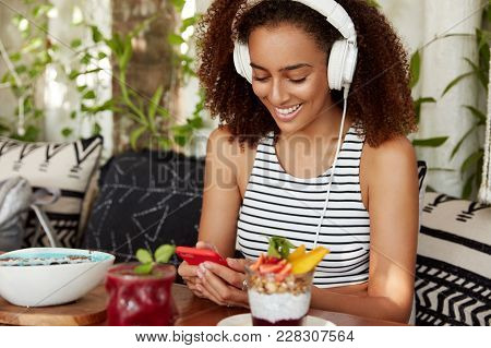African American Female With Bushy Hairstyle, Listens Online Radio Broadcast In Headphones, Connecte