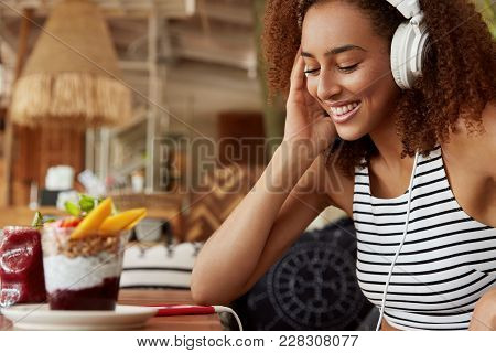 Happy Young African American Female In Headphones Searches Music On Internet Website For Uploading I