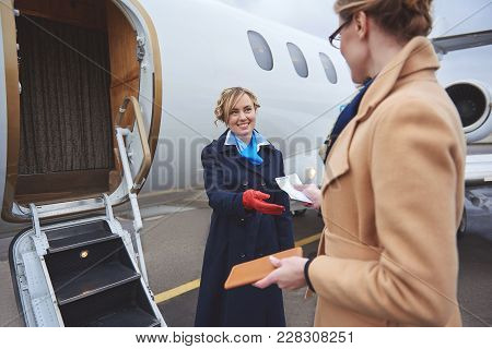 Outgoing Air-hostess Taking Tickets From Businesswoman While Situating Near Plane. Occupation Concep