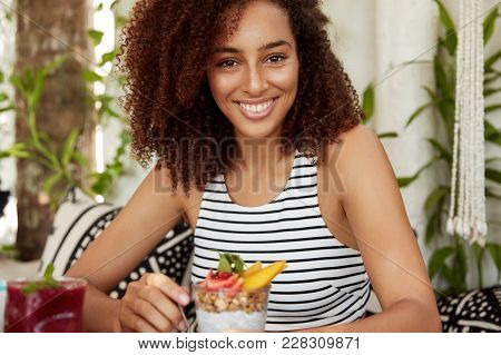Cropped Shot Of Glad Carefree Dark Skinned Female Recreats At Cozy Cafeteria, Tastes Delicious Exoti