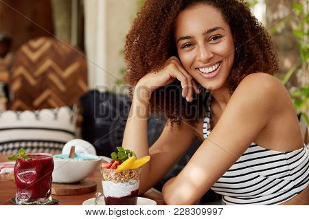 Sideways Portrait Of Cheerful Attractive Young Dark Skinned Female With Bushy Hairstyle, Eats Desser