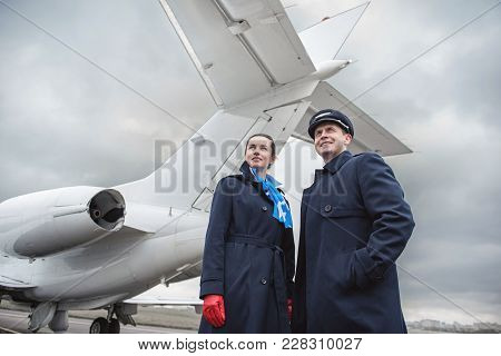 Low Angle Portrait Of Cheerful Air-hostess And Glad Pilot Locating Near Airplane Outdoor. Profession