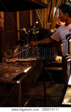 Siem Reap, Cambodia- March 22, 2013: Unidentified Khmer Boy Cooks On Grill In Cambodia. Khmer People