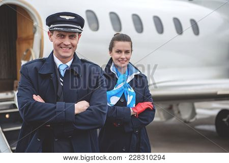 Portrait Of Cheerful Pilot And Happy Air-hostess Looking At Camera While Locating Opposite Airplane.