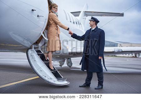 Side View Beaming Aviator Helping Cheerful Lady Going Down From Aircraft. Profession And Journey Con