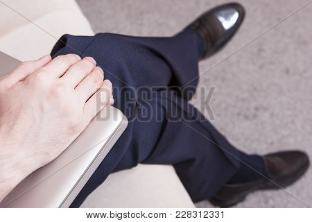 Body Parts. Closeup Of Hands Of Young Caucasian Man In Formal Wear And Penny Loeafers Holding Laptop