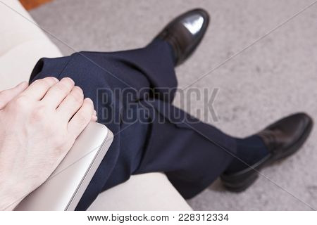 Closeup Of Hands Of Young Caucasian Man In Formal Wear And Penny Loeafers Holding Laptop On Knees. F