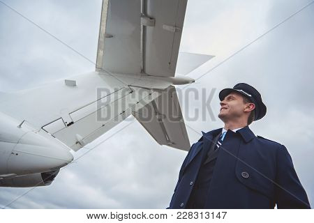 Low Angle Side View Cheerful Aviator Looking At Aircraft While Situating Near On Street. Profession