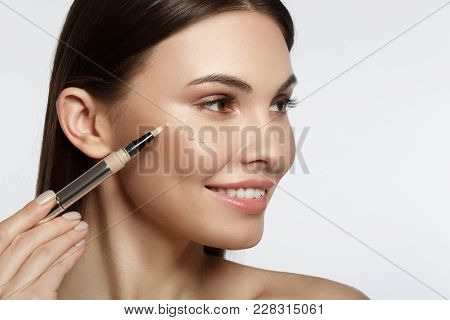 Joyful Young Woman Using Concealer And Smiling. She Is Holding Special Brush Near Her Face. Drops Of