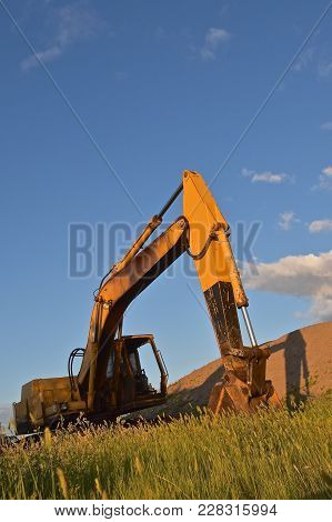 An Old Excavating Machine Casts Part Of It`s Shadow On A Sandpile.