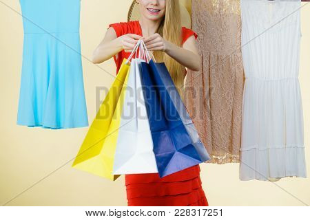 Woman In Clothes Shop Store Holding Shopping Bags Picking Summer Perfect Outfit, Dress Hanging On Cl