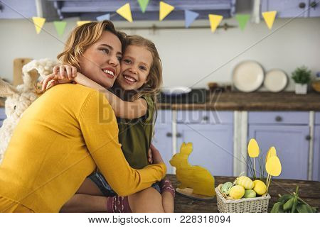 Portrait Of Smiling Girl In Festively Decorated Kitchen Hugging Her Mother. Rabbit Statuette And Bas