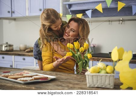 Glad Lady Sitting At Kitchen Table With Little Girl And Holding Spring Flowers. Daughter Is Hugging