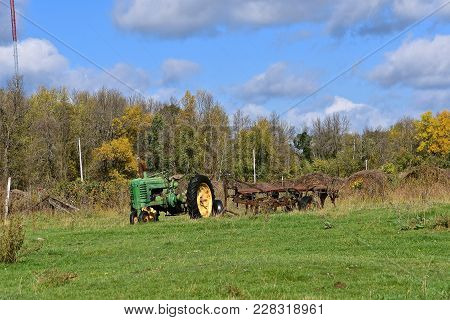 Bemidji, Minnesota,september 26, 2017. The Worn Out Old John Deere Tractor  Left In A Field Is A Pro