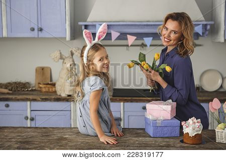 Waist Up Portrait Of Pleased Woman And Her Daughter In Country Style Kitchen. Mother Is Holding Bunc