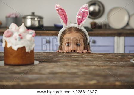 Curious Small Girl In Bunny Ears Peeking Out From Behind Kitchen Table With Tasty Easter Cake And Lo