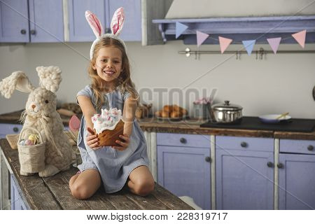 Portrait Of Glad Female Child In Bunny Ears Headband Sitting On Kitchen Bar Table With Big Rabbit To