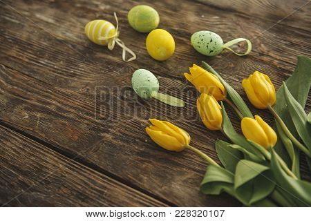 Close Up Of Spring Florets And Decorative Eggs Lying On Wooden Desk. Copy Space In Left Side