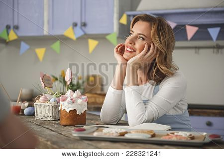 Delighted Young Woman With Pensive Expression Reposing In The Kitchen. Traditional Easter Food Stand
