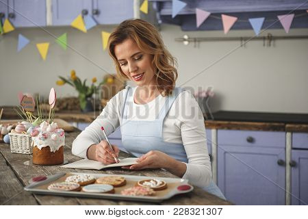 Satisfied Female Person Enjoying Holiday. She Is Resting In The Kitchen And Writing In Copybook With