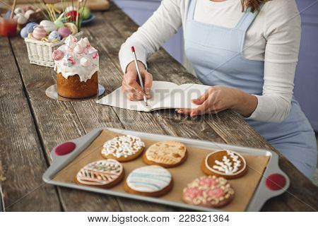 Lady Sitting At Ligneous Table And Writing In Notebook. Holiday Food Standing On The Desk