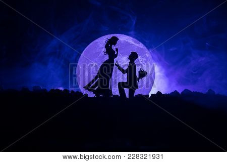 Amazing Love Scene. Silhouettes Of Man Making Proposal To Woman Or Silhouettes Of Couple Against Big