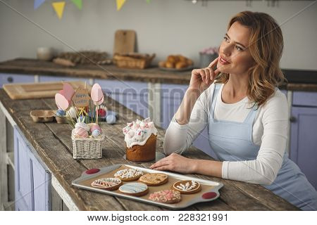 Pensive Female Person Sitting At Home And Looking Aside. Easter Confection Standing On The Table