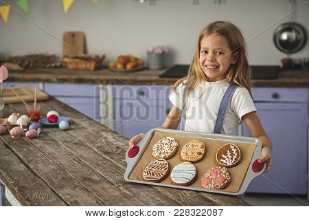 Portrait Of Smiling Little Girl Standing Near Wooden Kitchen Table And Demonstrating Salver With Eas