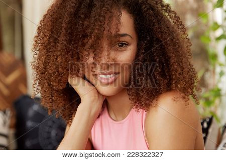Close Up Shot Of Attractive Woman With Curly Hair And Dark Skin, Has Positive Expression, Spends Spa