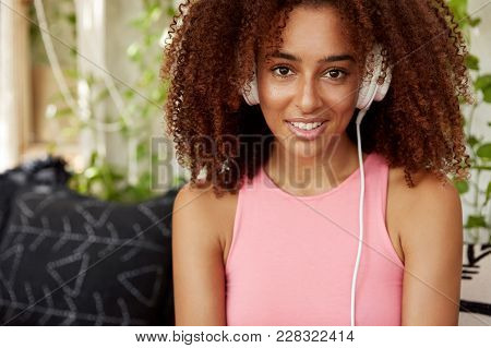 Confident Dark Skinned Attractive African American Womann In Pink Casual T Shirt, Listens Song Onlin