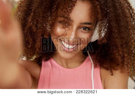 Portrait Of Curly Beautiful African American Woman In Headphones, Enjoys Favourite Music, Makes Phot