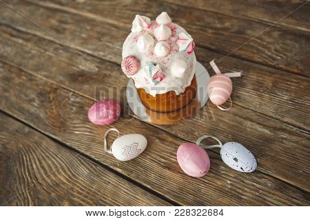 Close Up Of Sweet Bakery With Candies On The Top Standing On Wooden Board. Painted Eggs Lying Nearby
