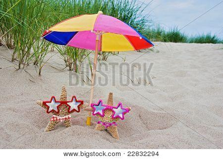 Pair of starfish in bikini under a colorful umbrella. poster