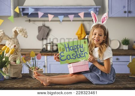 Full Length Portrait Of Content Child Relaxing In The Decorated Kitchen. She Is Holding Poster With