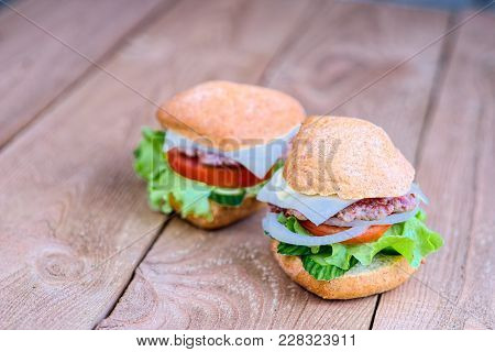A Two Craft Beef Burgers On Wooden Table Isolated. Close - Up View Of What Is Burger-lettuce, Onion,